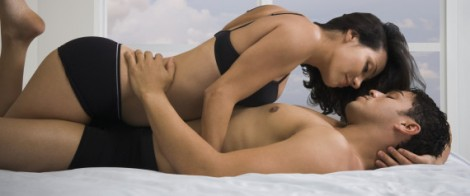 Hispanic couple hugging on bed